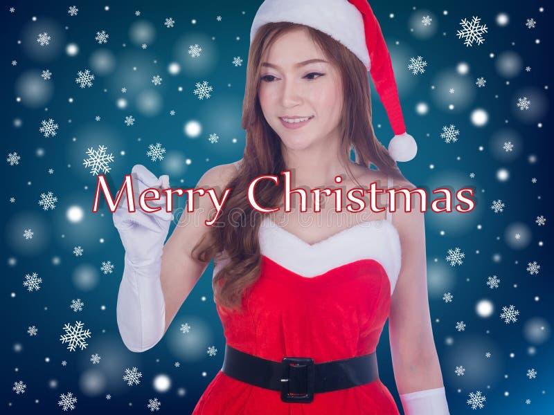 微笑圣诞节的妇女写圣诞快乐 免版税库存照片