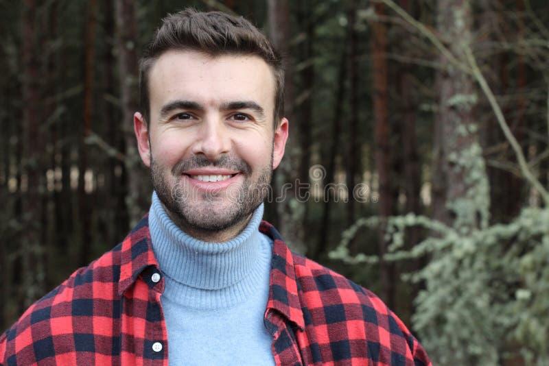 微笑在一个冬天的人看森林 免版税库存图片