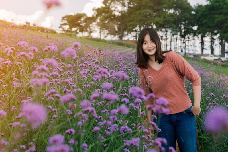 微笑在一个紫色花园里的亚洲妇女身分在雾和早晨阳光愉快的表示中间 库存照片