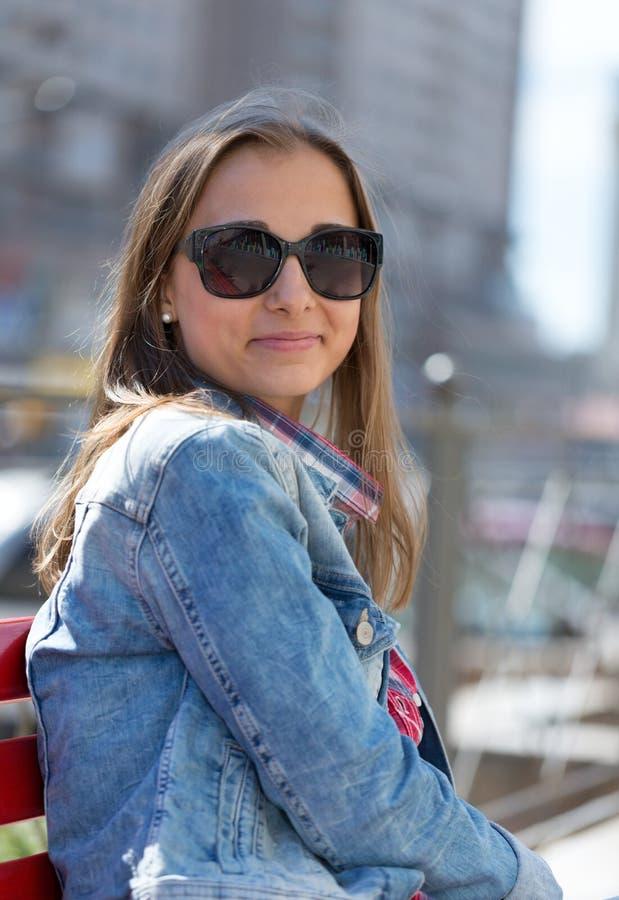 微笑在一个晴天的年轻美丽的时髦的女孩 库存照片