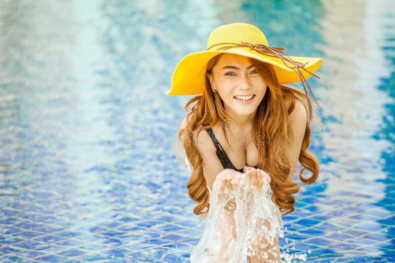 微笑在与叫喊的一个游泳池的美丽的年轻亚裔妇女 免版税库存照片