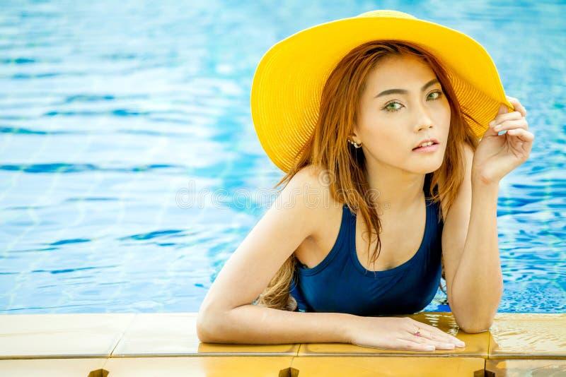 微笑在与叫喊的一个游泳池的美丽的年轻亚裔妇女 图库摄影