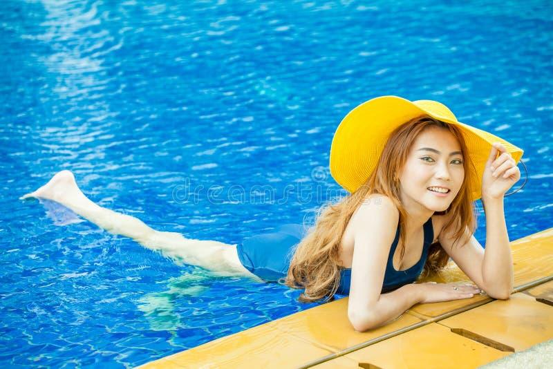 微笑在与叫喊的一个游泳池的美丽的年轻亚裔妇女 库存图片