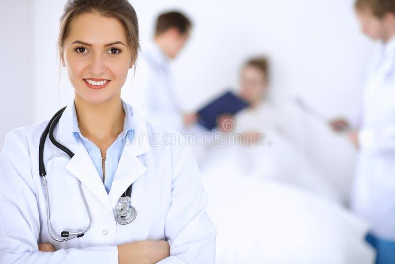 微笑在与患者在床上和两位医生的背景的女性医生 免版税库存图片