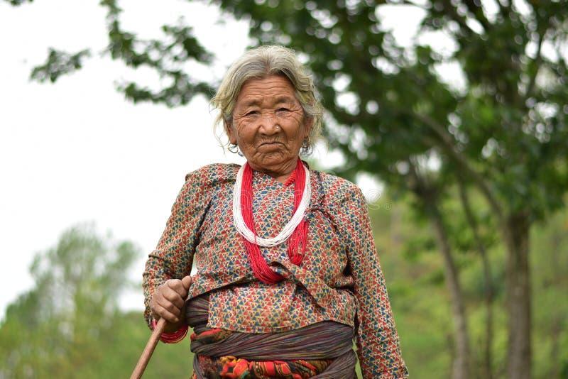 微笑在从尼泊尔的传统tamang礼服的一个美丽的老妇人 库存照片