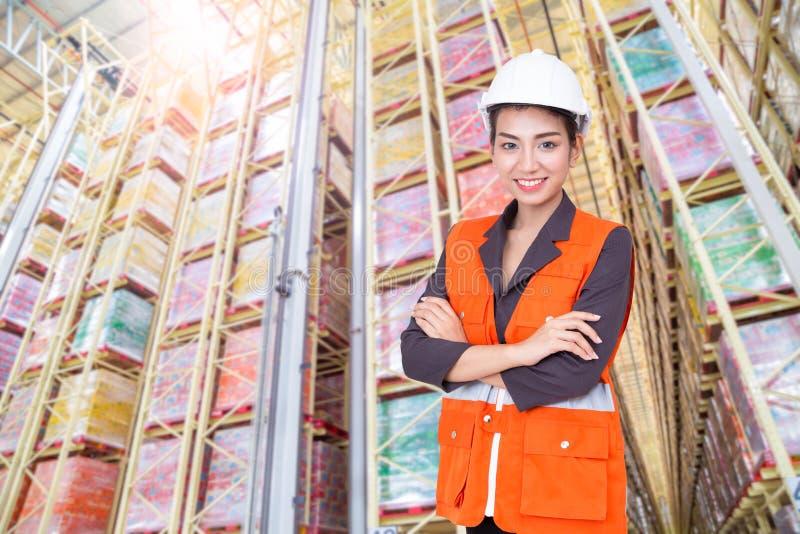 微笑在仓库里的女商人 库存照片