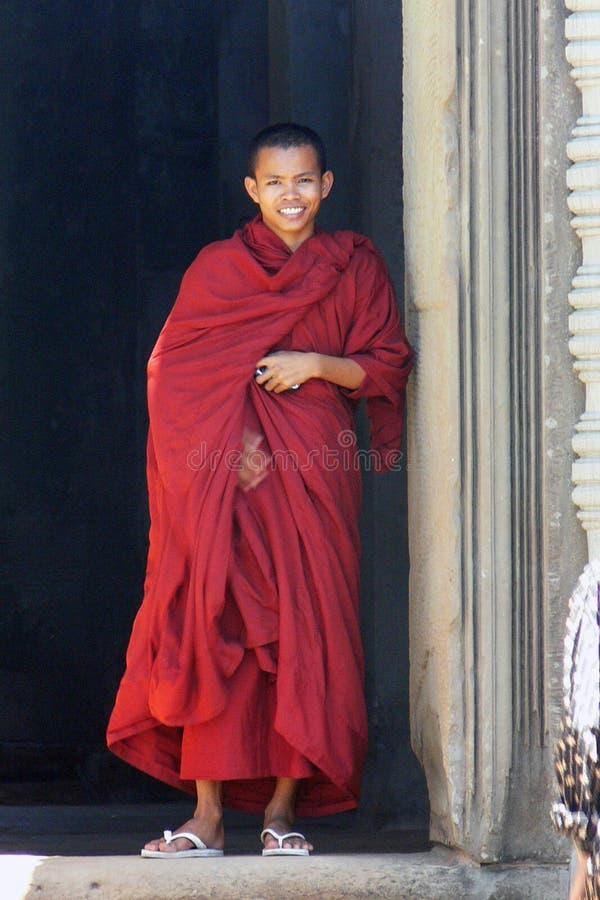 微笑在他的红色礼服的年轻高棉修士在吴哥,柬埔寨 免版税图库摄影