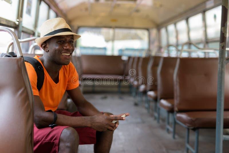 微笑在公共汽车上的体贴的年轻愉快的非洲黑人旅游人 免版税库存照片