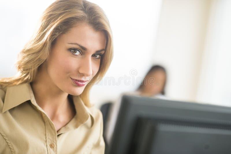 微笑在办公室的美丽的年轻女实业家 图库摄影