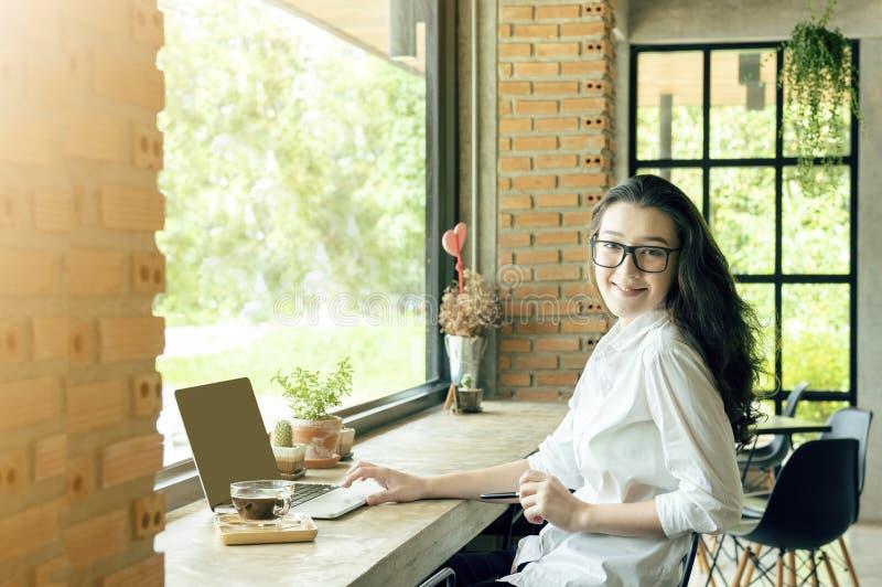 微笑在咖啡馆咖啡馆,手用途膝上型计算机,葡萄酒颜色口气的亚裔妇女画象 电子商务,大学教育,互联网 免版税图库摄影