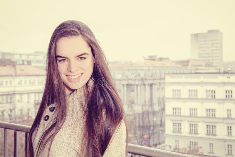 微笑在城市背景中的俏丽的妇女画象 免版税库存照片