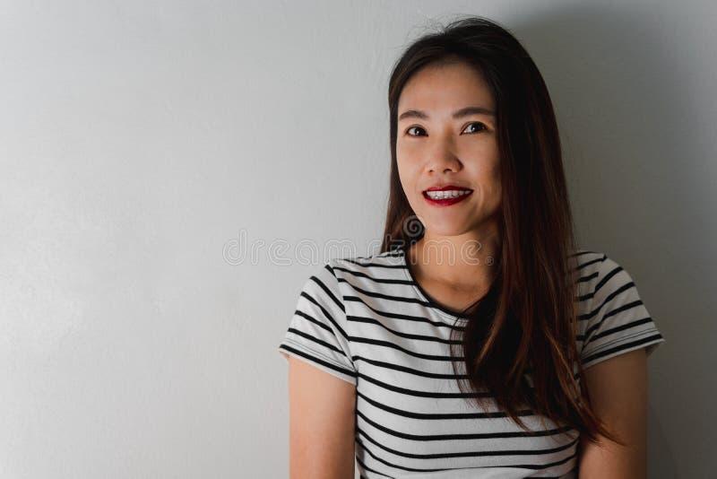 微笑在墙壁背景的美丽的年轻亚裔妇女 免版税库存图片