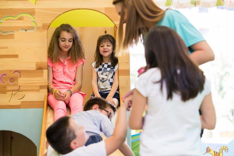 微笑在娱乐时间期间的逗人喜爱的女孩监督由一位年轻老师 免版税库存照片