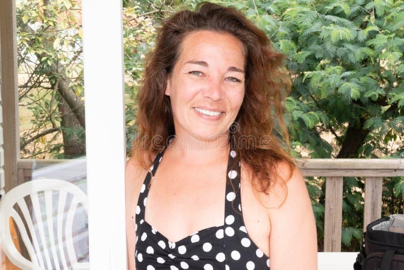 微笑在室外大阳台的美丽的中间年迈的妇女 免版税库存图片