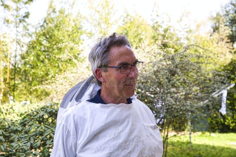 微笑在工作以后的一位年长蜂农的画象,在绿色背景 免版税库存照片