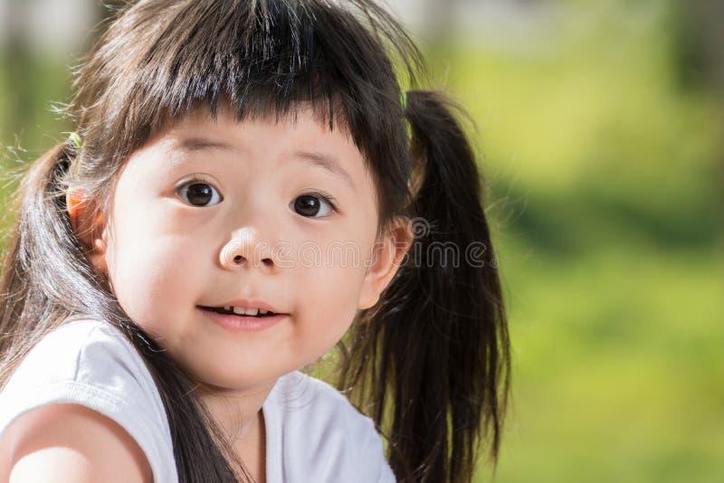 微笑在庭院里的逗人喜爱的亚裔女婴 免版税库存照片