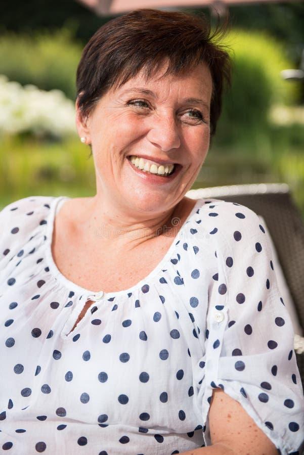 微笑在庭院里的画象可爱的妇女 免版税库存图片