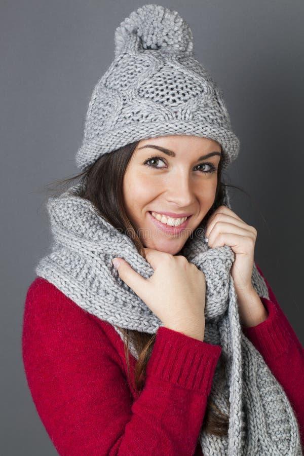 微笑在拿着的愉快的女性少年她温暖的冬天围巾 免版税图库摄影