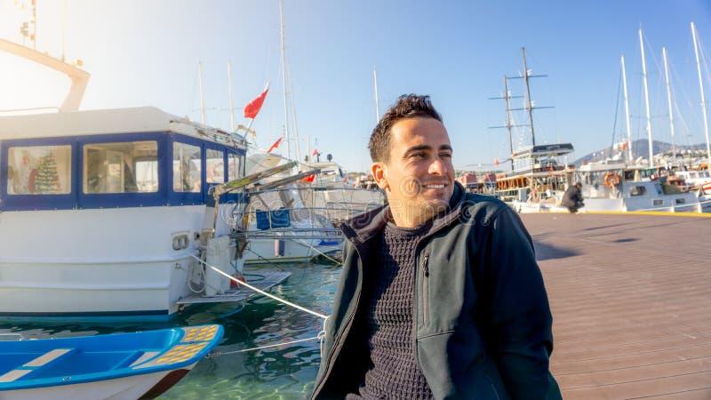 微笑在日落期间的年轻土耳其旅游人在博德鲁姆小游艇船坞,土耳其 帆船、水手和晴天 免版税图库摄影