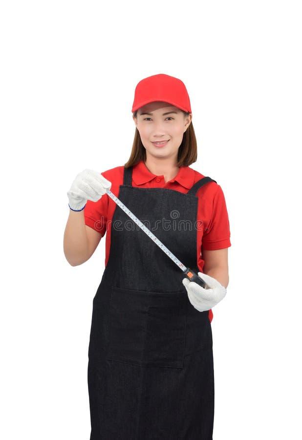 微笑在有围裙的,在白色backround隔绝的手套手藏品测量的磁带红色制服的年轻女人工作者画象 库存照片