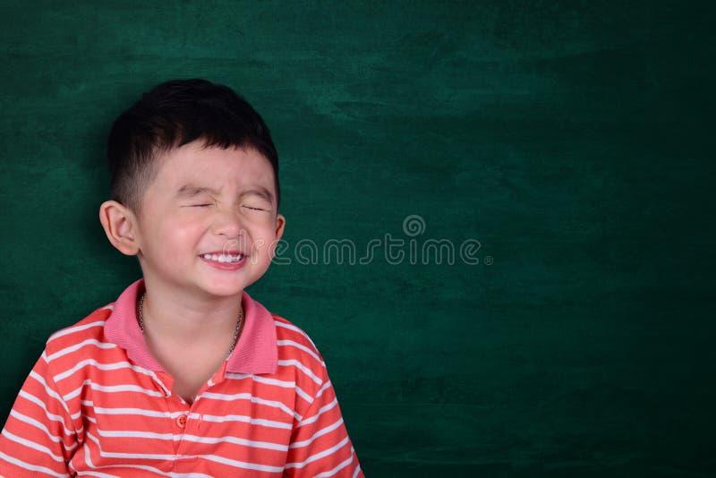 微笑在有拷贝spac的空的绿色黑板的愉快的亚洲孩子 图库摄影