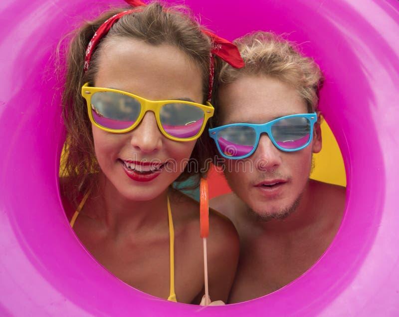 微笑在桃红色可膨胀的圆环中间的滑稽的年轻愉快的海滩夫妇 库存图片