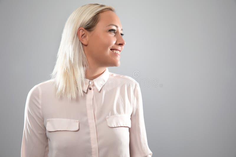 微笑在桃红色衬衣的愉快和自然女性白肤金发的模型 免版税库存照片