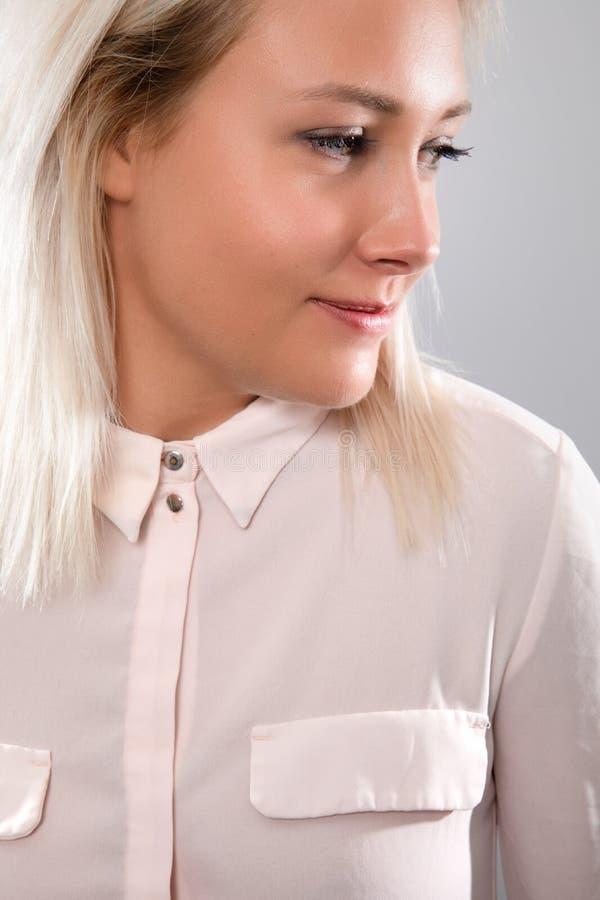 微笑在桃红色衬衣的愉快和自然女性白肤金发的模型 免版税图库摄影