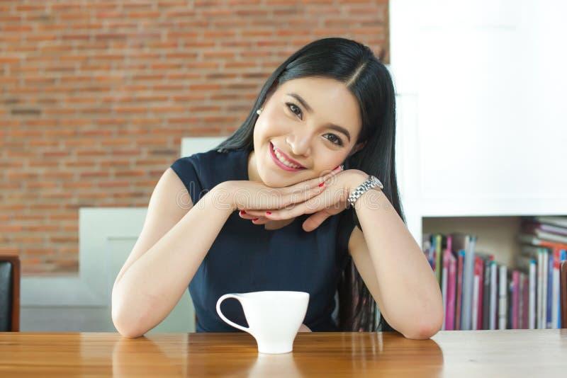 微笑在桌上的咖啡前面的亚裔妇女 库存照片