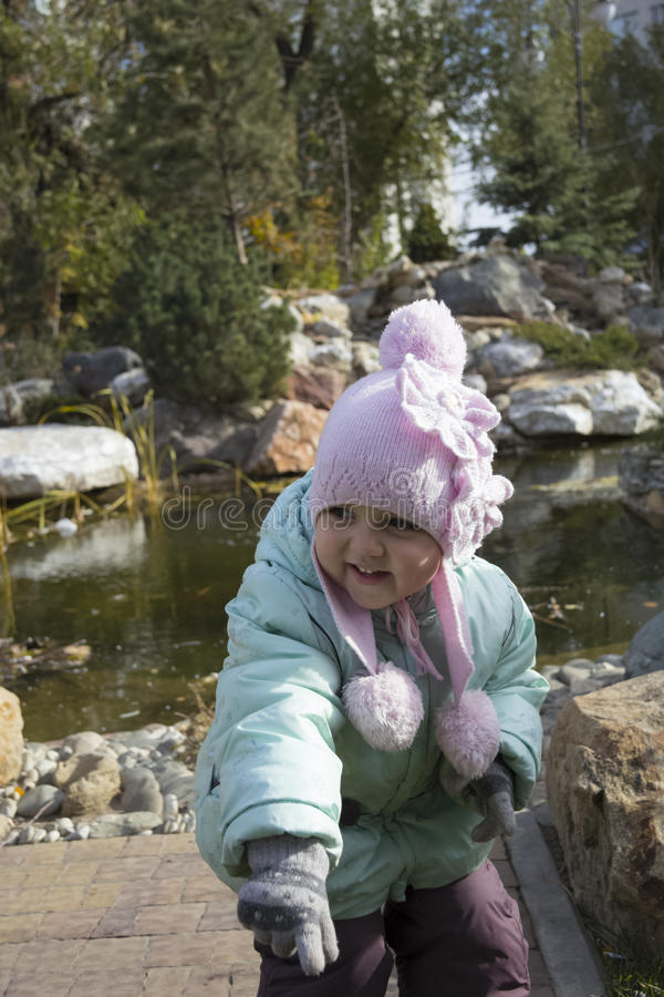 微笑在池塘附近的女孩 免版税库存图片
