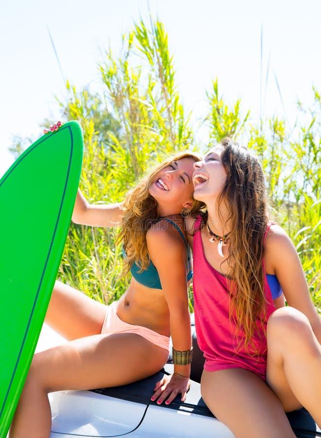 微笑在汽车的愉快的疯狂的青少年的冲浪者女孩 免版税库存图片