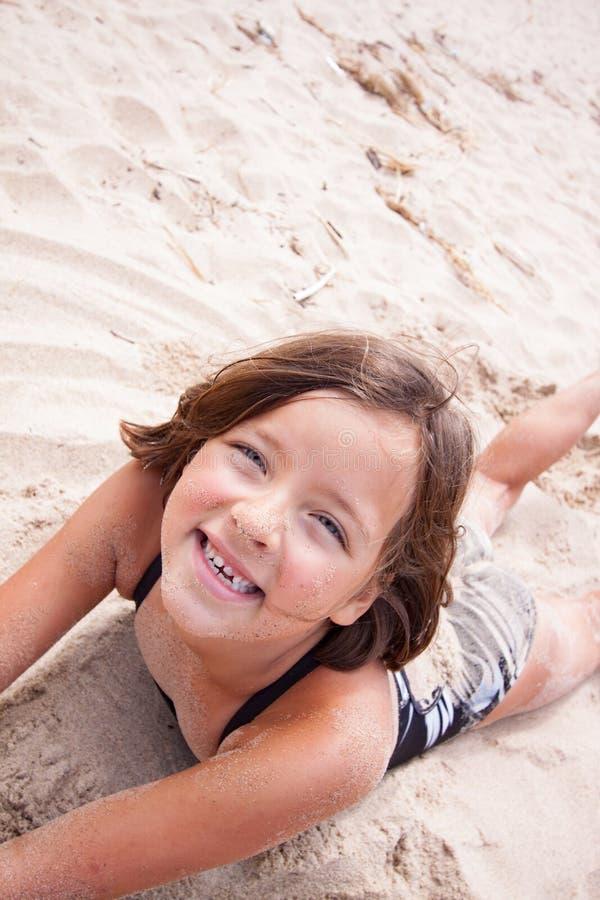 微笑在沙子的女孩 免版税库存照片