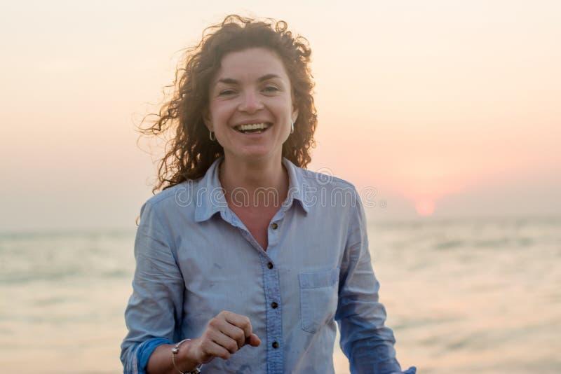 微笑在海滩的愉快的俏丽的年轻性感的红色头发妇女 免版税库存照片