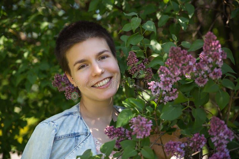 微笑在淡紫色开花的树下的美丽的逗人喜爱的女孩 图库摄影