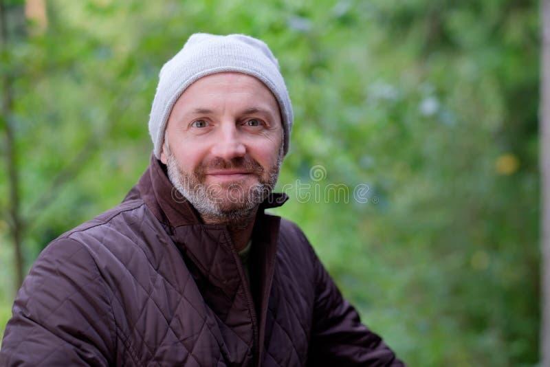 微笑在温暖的帽子和夹克的英俊的成熟人看照相机 免版税库存图片