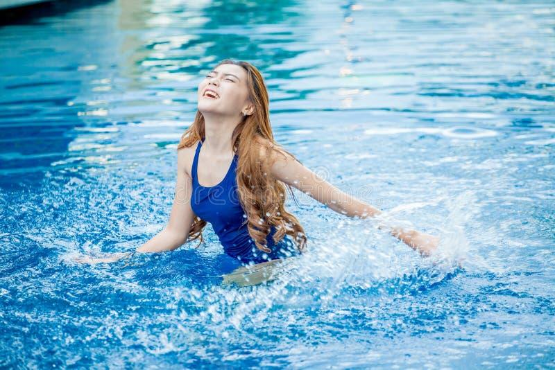 微笑在游泳池飞溅的美丽的年轻亚裔妇女 免版税库存照片