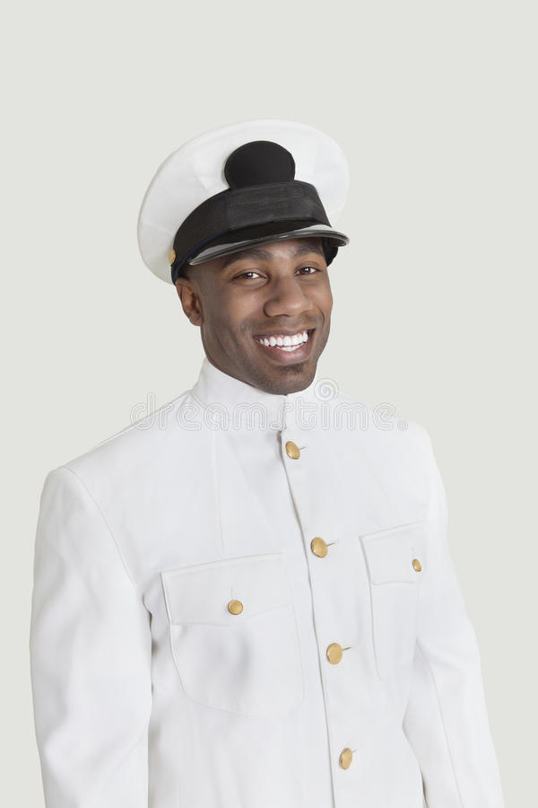 微笑在灰色背景的一名年轻非裔美国人的美国海军官员的画象 库存图片