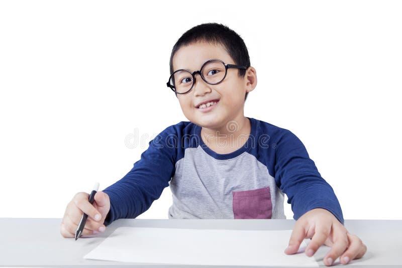 微笑在照相机的聪明的男小学生 库存图片