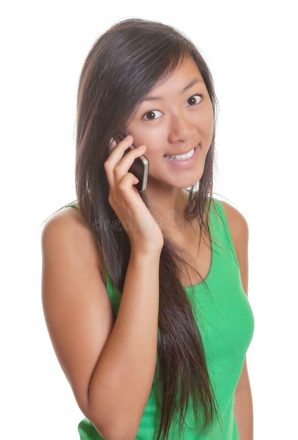 微笑在电话的亚裔女孩 免版税图库摄影