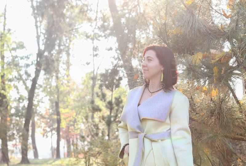 微笑在秋天的美丽的年轻女人在公园 华美的愉快的女孩特写镜头画象叶子的在晴朗的秋天天 库存图片