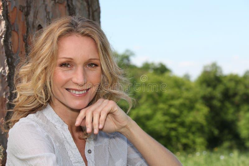 微笑在结构树下的妇女 免版税库存图片
