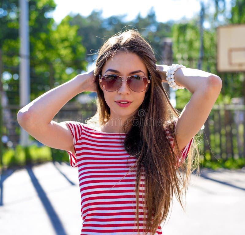 微笑在自然摆在太阳镜,时尚生活方式,一的愉快的聪慧的年轻美丽的女孩户外停放 库存图片