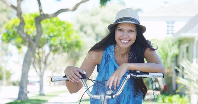 微笑在自行车的少妇 免版税库存照片