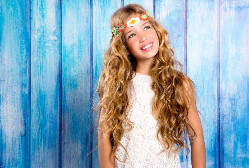 微笑在蓝色木头的白肤金发的愉快的嬉皮儿童女孩 免版税图库摄影