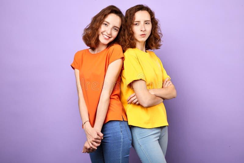 微笑在蓝色背景的两快乐的正面女孩孪生 图库摄影