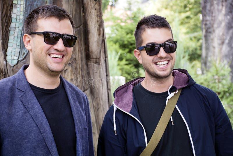 微笑在街道上的两个美丽的年轻人画象  图库摄影