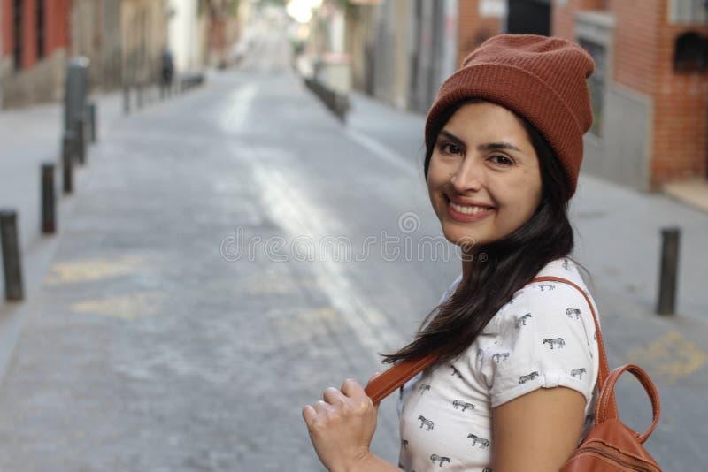 微笑在街道上的坚定的种族妇女 免版税库存图片