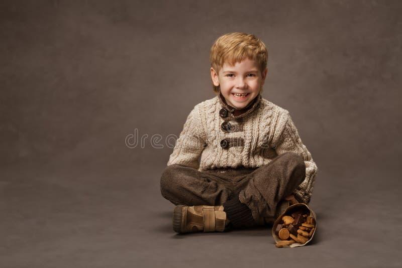 微笑在被编织的毛线衣的孩子。在减速火箭的样式的男孩时尚。增殖比 库存图片