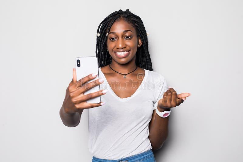 微笑在视频通话期间的笑的非洲少女 做selfie的乐观黑人夫人室内照片在白色背景 免版税库存照片
