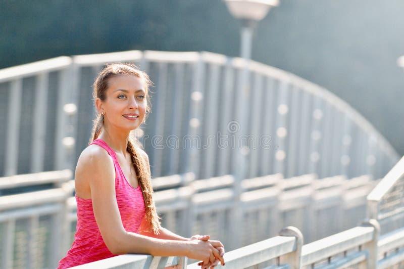 微笑在都市金属城市桥梁的少妇画象在连续锻炼以后 库存图片